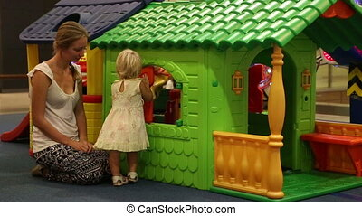 child plays with mother at colorful toy house