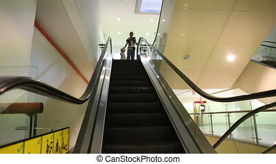 mother and daughter get down the escalator - young mother...