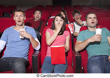Young people  watching a movie at the cinema