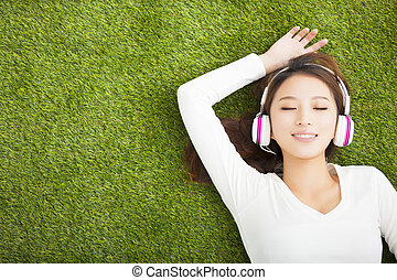 Relaxed woman listening to the music with headphones lying on th