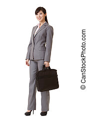 Asian business woman standing and holding briefcase, full...