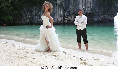 blonde bride in white dress flirts with groom against cliff...