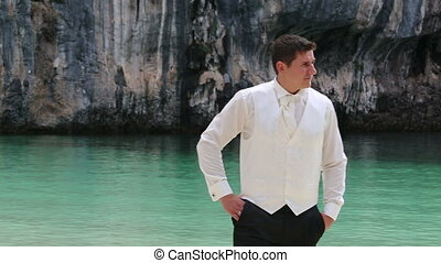 groom in black trousers and white shirt vest and tie walks...