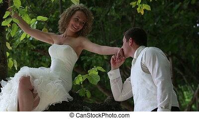 handsome groom kisses blonde bride hand