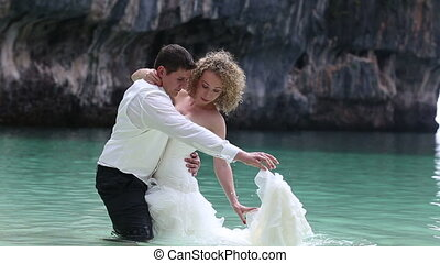 bride and groom stand in shallow water at beach and put dress on water