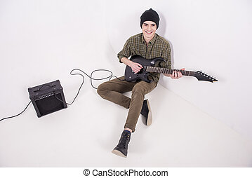 Man with guitar - Young male musician is playing a...