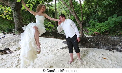 blonde bride siting on tree and flirt with  groom