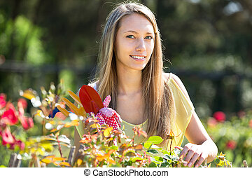 woman at garden - smiling woman in roses plant at garden