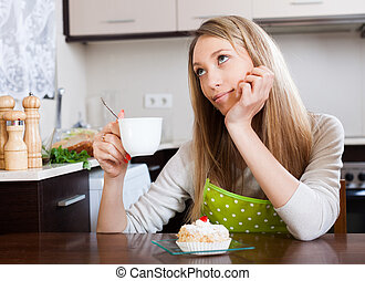 woman drinking tea with cake at table