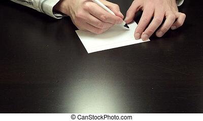 Written note Money - Man hands write the word Money on white...