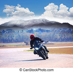 young man riding motorcycle on asphalt road against mountain...