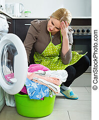 Tired woman doing laundry - Tired young woman doing laundry...