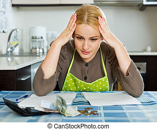 Sad woman calculating family budget - Sad woman calculating...