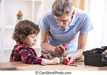Grandfather and grandson are measuring a board with...