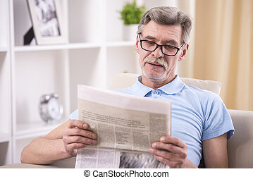 Grandfather and grandson - Senior man is reading newspaper...