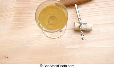 Corkscrew, cork and glass of white wine are spinning on a...