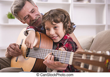 Grandfather and grandson - Grandfather is playing guitar...
