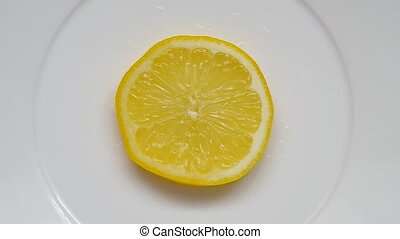 Sliced lemon rotate on a plate.