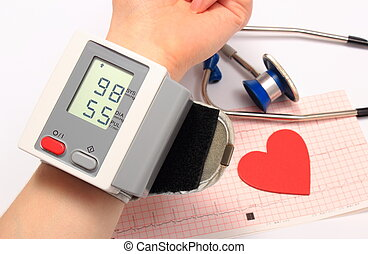 Measuring blood pressure, heart shape and stethoscope on electrocardiogram