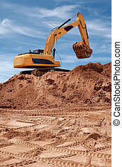Excavator bulldozer in sandpit with raised bucket filled of...
