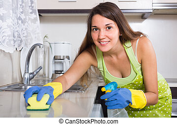 Woman cleaning kitchen - Smiling young woman cleaning...
