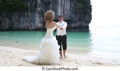 bride and groom turn round together - blonde bride and...