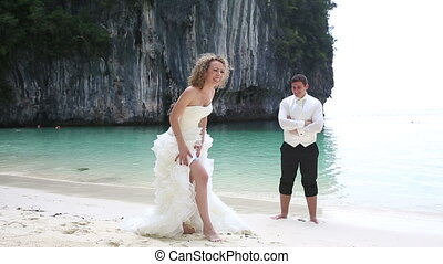 blonde bride in white dress poses and smile near groom...