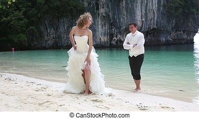 bride in white dress flirts with groom embracing her