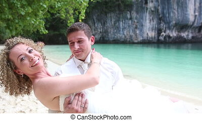 strong groom holds in arms blonde bride in wedding dress...