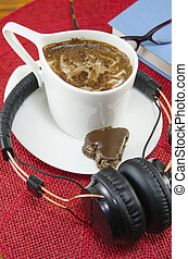 Cup of coffee and headphones, book and glasses on a red...