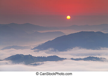 Amazing dawn sky over the misty mountains