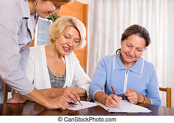 women consulting at insurance agent - Happy mature women...