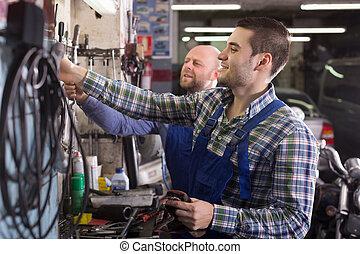 Two garage workmen near facilities - Portrait of two...