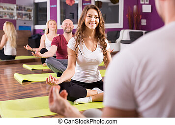Adults having yoga class - Happy smiling young adults having...