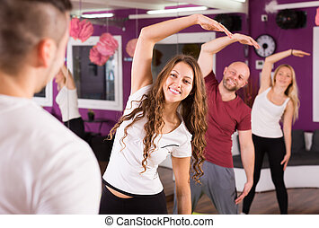 Adults having group fitness class - Happy adults having...