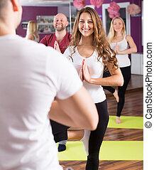 Adults having yoga class - Happy young adults having yoga...