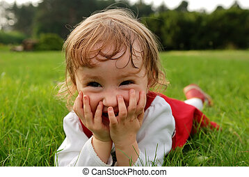 Close-up view of little girl laughing with hands on the mouth