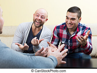 Guys sitting at table, chatting and smiling at home