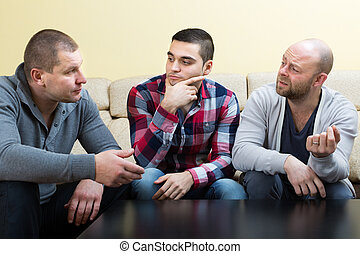 Guys sharing problems at the table - Three guys sitting at...