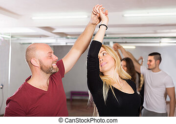 Couples enjoying of partner dance - Smiling young couples...