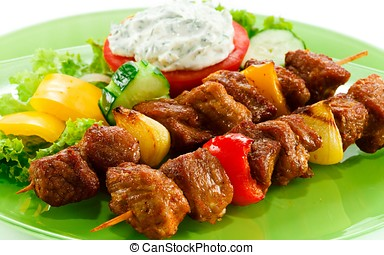 Kebab with vegetables on a plate closeup