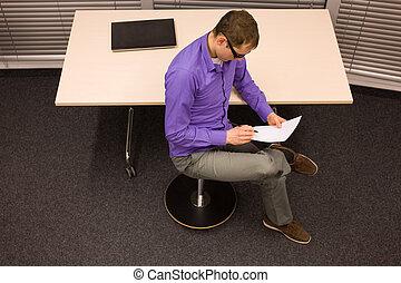 man reading  sitting on stool