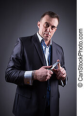 male gangster in a business suit with a knife - adult male...