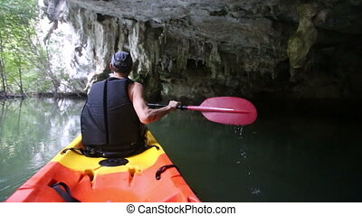 man rows kayak in cliff cave - strong elder man rows kayak...
