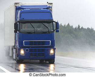 Blue Lorry on wet road - blue lorry with white trailer...