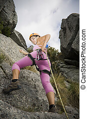 Woman in rappel - Youn woman descending in rappel with...