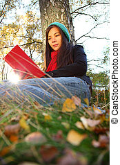 Woman reading - Reading outdoors in Autumn Beautiful young...