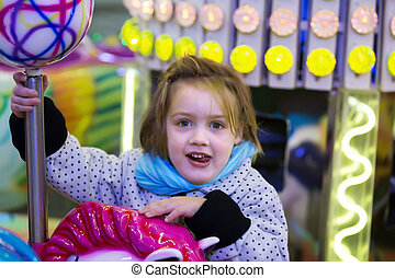 child on wooden horses at carousel