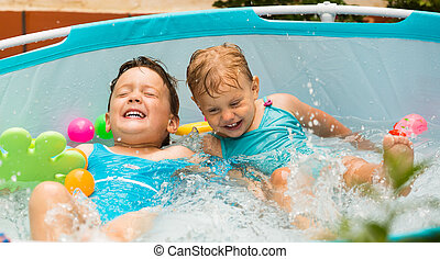 Children swimming in kid pool - Excited laughing children...