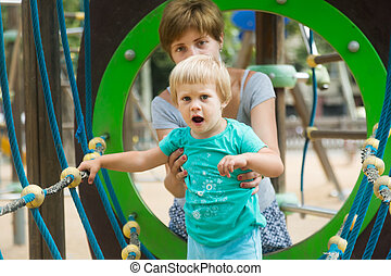 girl with mother at action-oriented playground in summer